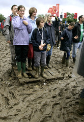 Revellers stand in the mud during the Glastonbury music festival in Somerset