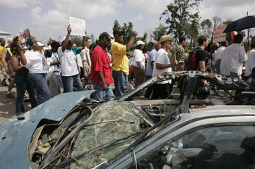 Participants pass a destroyed car during a march commemorating the first anniversary of Hurricane Katrina in the Lower Ninth Ward of New Orleans