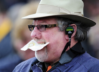 Punter holds ten pound note in his mouth as he watches horses at Cheltenham Festival horse racing meeting in Gloucestershire