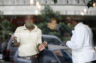 People watch from inside shop as riot police disperse opposition supporters in downtown Nairobi