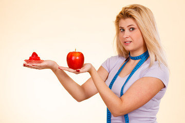 Woman with measuring tape choosing what to eat