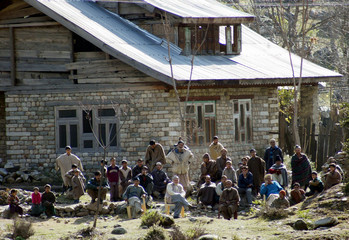 INDIAN KASHMIRI RESIDENTS SIT OUTSIDE THEIR HOUSE ON THE INDIAN SIDE OF THE BORDER IN TITHWAL VILLAGE.
