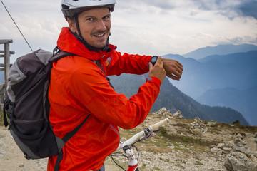 Mountainbiker am Berg mit GPS-Uhr