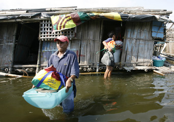 Residents wade through knee-deep waters as they carry their belongings in Paranaque city, south of Manila