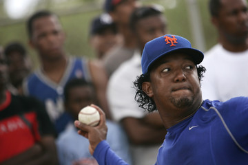 Dominican Republic's Pedro Martinez of the New York Mets pitches during a training session, while fans watch, in an open camp in Boca Chica