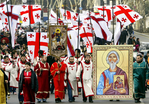 Georgians march with icons and national flags along the street in central Tbilisi to celebrate Orthodox Christmas