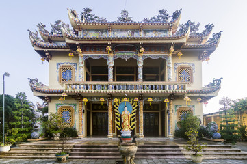 Exterior facade view of typical vietnamese Quang Minh Mahayana Buddhist temple with standing Amitabha Buddha statue on the entrance located in Da Nang, Vietnam