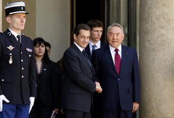 France's President Sarkozy shakes hands with his Kazakh counterpart Nazarbayev  as he leaves the Elysee Palace in Paris after a meeting