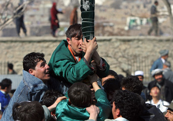 Afghan men try to kiss religious flag during the Afghan New Year Day in Kabul