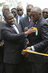 Ivory Coast's President Gbagbo receives a piece of ribbon in colours of the national flag in Yamoussoukro