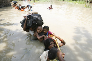 Flood-affected people hold their belongings as they wait to be evacuated by a rescue team at Chondipur village in Bihar