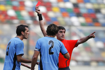 Uruguay's Diego Godin receives a red card as teammate Diego Lucano argues with the referee during their World Cup 2010 qualifying soccer match against Peru in Lima