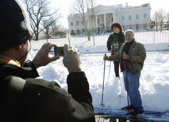 A man takes pictures of skiers in the snow in front of the White House in Washington