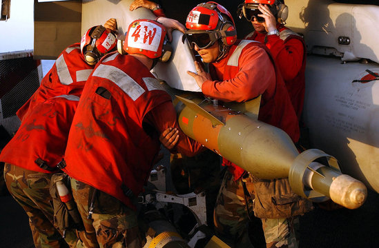 A laser guided 500 lb bomb is attached to an F/A-18C Hornet aboard the US Navy aircraft carrier USS ..