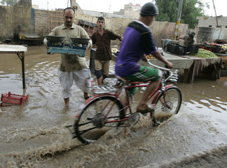 A resident rides his bicycle past vendors who are moving their goods from a flooded market during a rainy day in Najaf