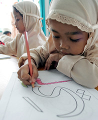 Indonesian Muslim girls practise colouring Arabic letters in Sukabumi