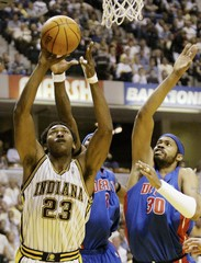 PACERS RON ARTEST FIGHTS FOR SHOT UNDER PRESSURE FROM PISTONS BEN WALLACE AND RASHEED WALLACE.