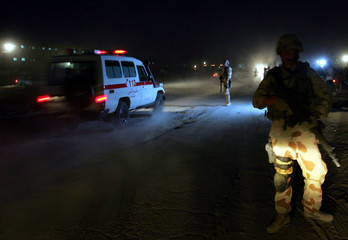 An ambulance drives to a bomb blast site as international peacekeepers stand guard in Kabul