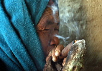 -PHOTO TAKEN 12FEB06- A Nepali woman smokes from an earthen pipe in the village of Tila, Rolpa distr..