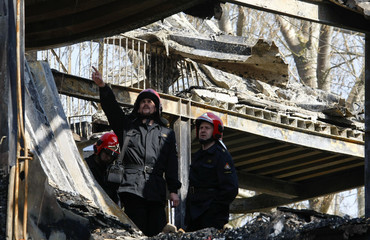 Firemen inspect the remains of burned out three-storey building in Kamien Pomorski