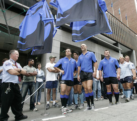 Super 14 rugby players Cannon, Turinui, Sharpe, Fitter, Waugh and Hewat walk near rugby jerseys in Sydney