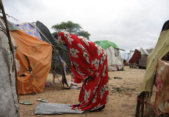 A displaced Kenyan woman offers afternoon prayers near her shelter at Hyuga girls primary school at River Tana in Garissa