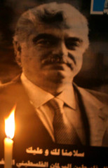 candle is lit near the pictures near the picture of slain Lebanese former Prime Minister Rafik ...