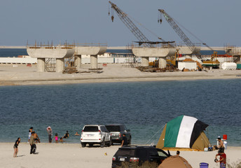 Beach goers enjoy UAE national day holiday as suspended work on Nakheel's Palm Jebel Ali is seen in the background in Dubai