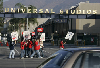 Members of the Writers Guild of America carry picket signs at one of the gates to Universal Studios in Los Angeles