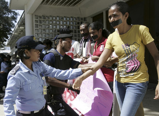 East Timorese police officers arrest students during a protest in Dili