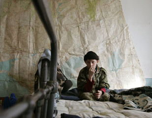 A boy sits on his bed in a military training camp in the village of Sengileevskoye