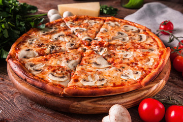 Appetizing italian food. Hot baked pizza with mushrooms and cheese served on wooden rustic table with ingredients.