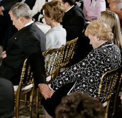 US President Bush holds hand with Florida woman during prayer at White House.