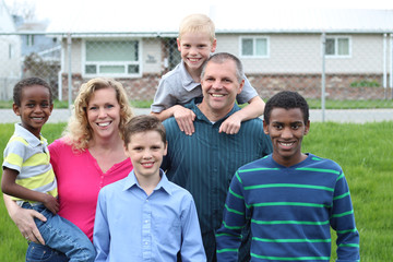 A multi-racial family, with the caucasian mother and father with their caucasian biological sons and their African adopted sons.
