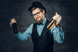 Bearded hipster male dressed in a blue shirt, elegant waistcoat and top hat holds two craft beer bottles.