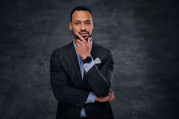 A stylish black male dressed in a suit over grey background.