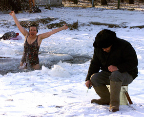 RUSSIAN WOMAN JUMPS INTO WATER AS FISHERMAN SITS ON ICE OUTSIDE MOSCOW.