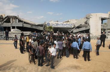 Journalists gather around former U.S. President Carter during visit at destroyed American International School in northern Gaza Strip