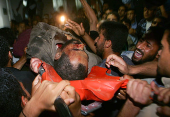 Palestinians carry body of Samhadana after he was killed by Israeli air strike in Rafah