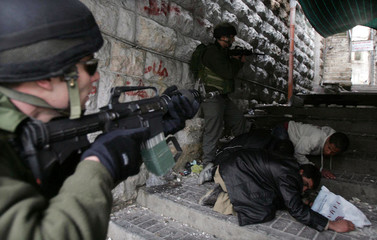 Israeli troops take up position as Palestinians take cover during clashes in the West Bank city of Hebron