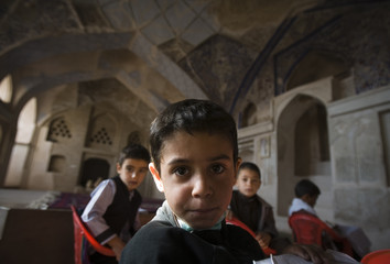 A Muslim Afghan schoolboy looks on as he sits in an old synagogue which is being used as a school in Herat
