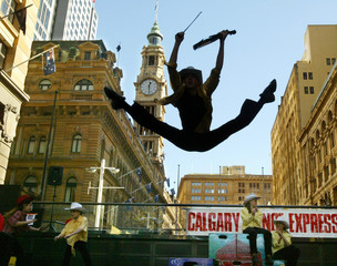 CANADIAN DANCER STEPHEN WELCH IS SILHOUETTED AGAINST CITY SKYLINE DURING A PERFORMANCE IN SYDNEY.