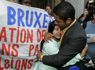 Ecuador's Cajamarca cries in the arms of her father Loja in Brussels