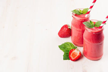 Red strawberry fruit smoothie in glass jars with straw, mint leaf, cut ripe berry. White wooden board background, copy space.