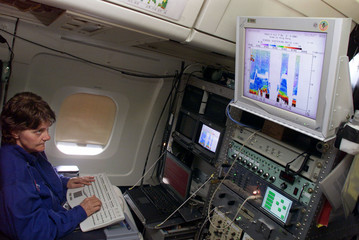 SCIENTIST STUDIES OZONE DATA ON NASA DC-8 PLANE IN HONG KONG.