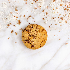 Chocolate chips cookie with flour on white marble