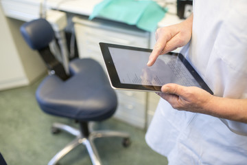 hands of a dentist working on a tablet computer