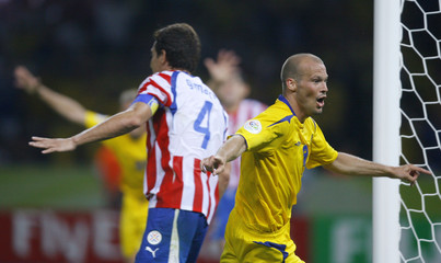 Sweden's Fredrik Ljungberg runs past Paraguay's Carlos Gamarra (L) as he celebrates his goal during their Group B World Cup 2006 soccer match in Berlin