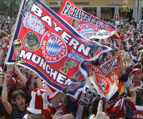 Supporters of Bayern Munich celebrate German first division soccer league Bundesliga champion trophy in Munich