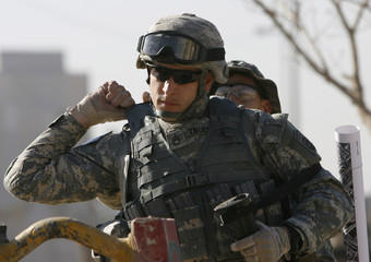 A U.S. soldier helps a fellow trooper adjust his flak jacket before going on a mission in Baghdad